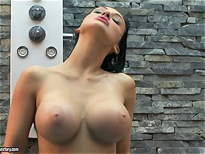 Aletta Ocean spray her globes with water from douche